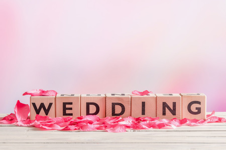 Wedding sign with rose leaves on a wooden table