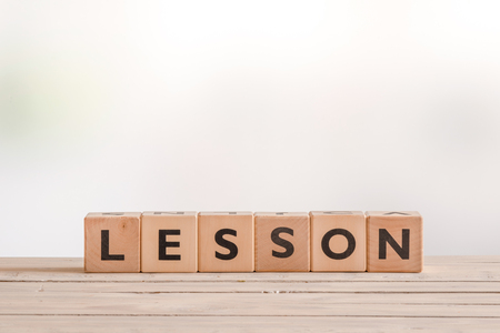 word lesson: Lesson word spelled with cubes on a wooden table