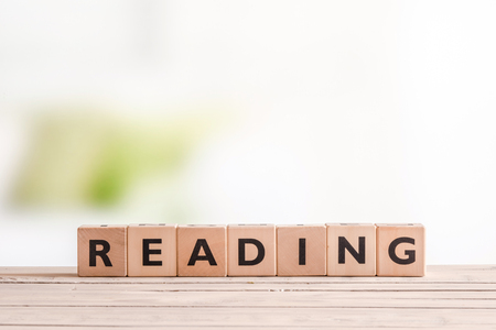 e books: Reading sign made of wood on a table