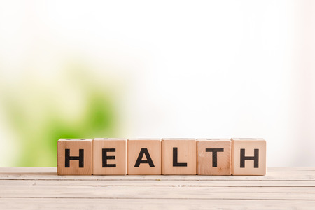 green living: Health sign made of wood on a natural desk Stock Photo