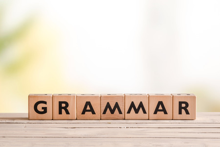 Grammatica teken gemaakt van hout op een schoolbank