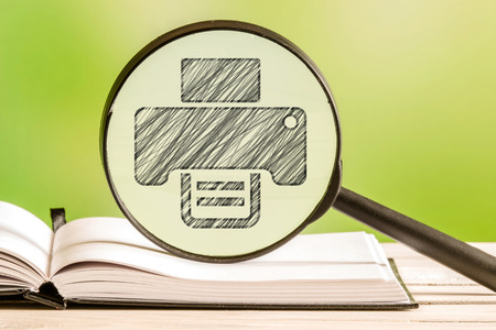 printer drawing: Printing service with a pencil drawing of a printer in a magnifying glass Stock Photo