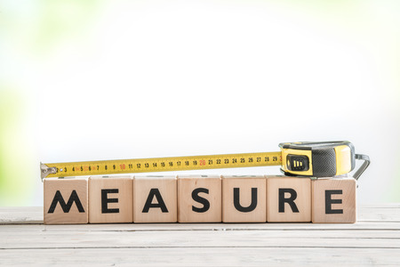 measurement tape: Cubes with the word measure on a table Stock Photo