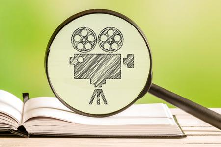 Búsqueda película con un dibujo de lápiz de un proyector de películas en una lupa Foto de archivo - 55221252