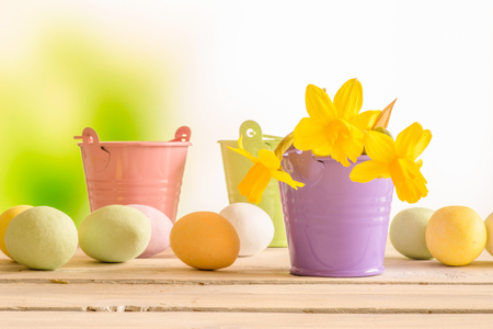 flowerpots: Easter eggs and flowerpots with daffodils on a wooden table Stock Photo