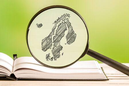 scandinavia: Scandinavia information with a pencil drawing of a scandinavian map in a magnifying glass