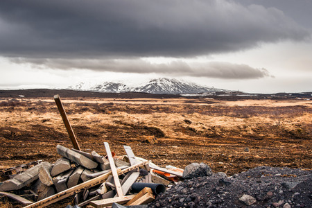 industry moody: Industrial materials on a rough field with mountains