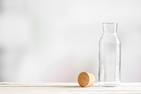 brown cork: Glass bottle with a brown cork on a wooden table Stock Photo
