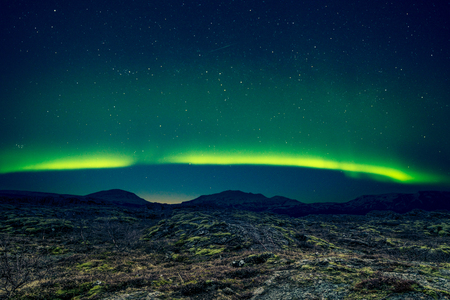 ionosphere: Northern lights over distant mountains in Iceland Stock Photo