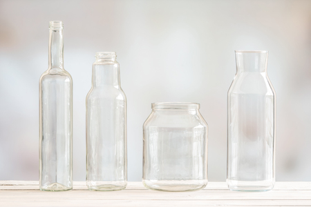 tare: Glass bottles on a row on a wooden table Stock Photo