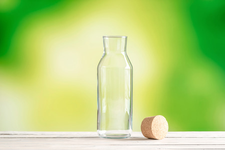 Empty glass bottle with a cork on green background