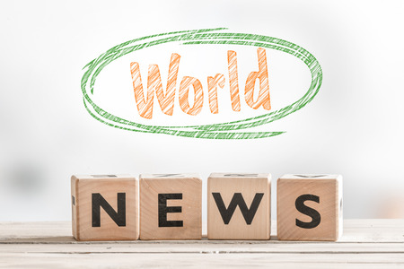 magazine stack: World news sign on a wooden indoor table