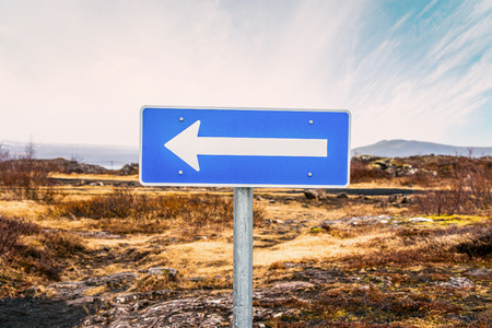 arrow sign: Sign with an arrow pointing left in a desert Stock Photo