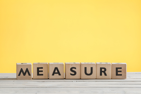 accomplishes: Measure sign with wooden cubes on a yellow background