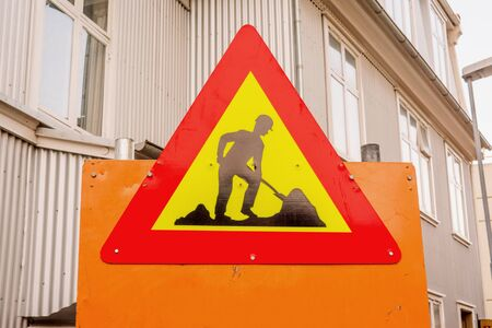 redirection: Under construction sign in a street with buildings