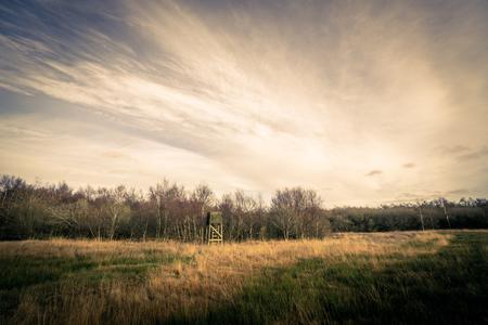 秋の風景のフィールドにハンティング タワー 写真素材