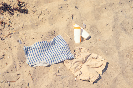 sun lotion: Kids clothes on a sandy beach with sun lotion