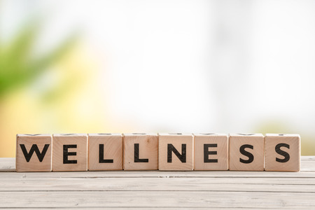 Wooden sign with the word wellness on a table Stock Photo