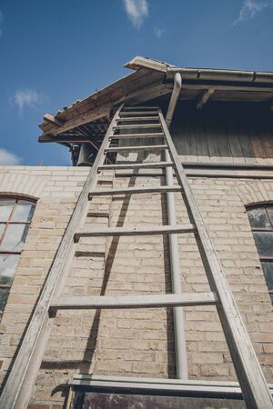 damaged roof: Tall ladder at an old building with damaged roof