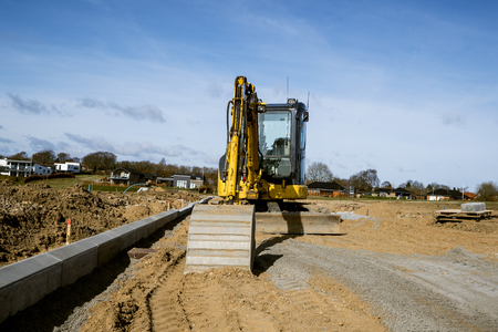 Yellow excavator digging on a construction site on a sunny day with blue sky Stock Photo