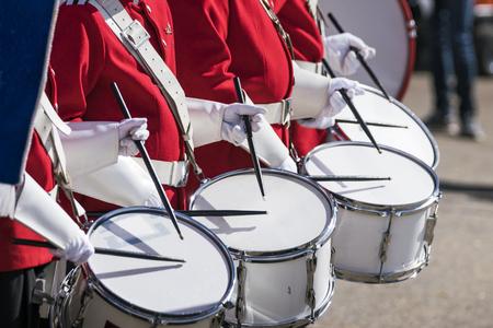 las baterías en uniformes rojos en una fila en un lugar de primavera con guantes blancos en las tambores