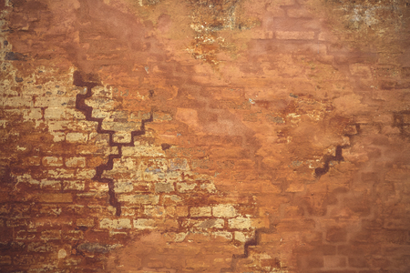 Orange wall in grunge look with peeling paint an an old brick house Stock Photo