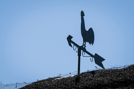 Weathervane silhouette of a rooster on a barnyard roof with blue sky in the background Фото со стока