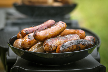 Grilled sausages on a plate at an outdoor barbecue kitchen with a stack of wieners 스톡 콘텐츠