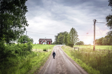 Young boy walking down a road in rural environment with a house at the end of the road