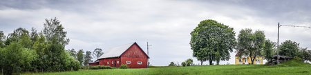 Classic red barn on a green field in a Swedish countryside landscape