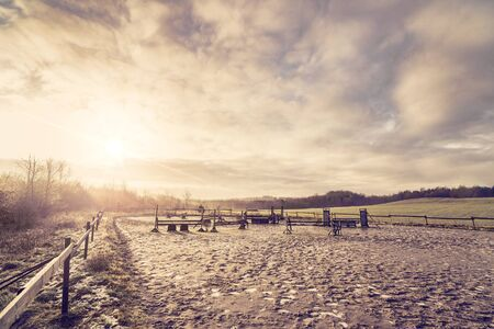Horse equestrian course in the morning sunrise with frost on the muddy ground