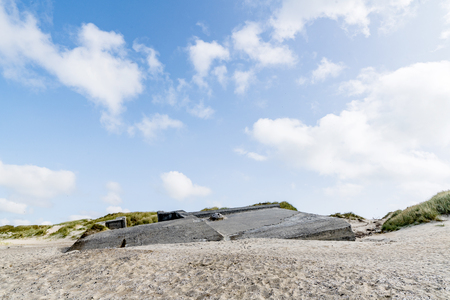 Ruin of a german bunker burried in the sand on a beach in Denmark on a summer day