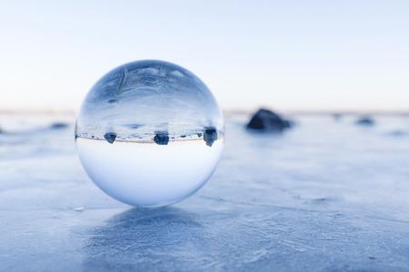 Black rocks in a glass orb on a frozen lake in the winter Banco de Imagens