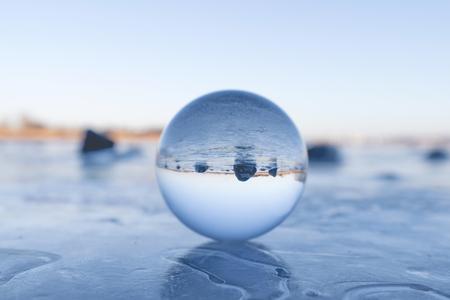 Kryształowa kula na zamarzniętym jeziorze w zimie z czarnymi skałami w tle