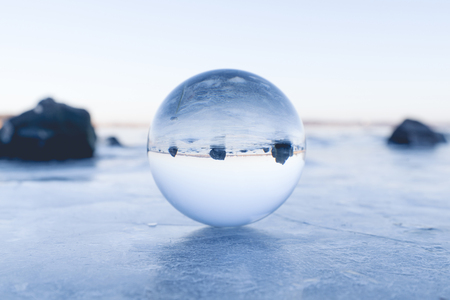 Glass orb balancing on ice on a frozen lake in the morning sunrise