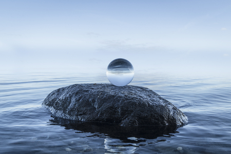 Crystal orb on a large black rock by the blue ocean on a silent morning