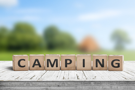 Camping word on a wooden cube sign with a blurry background of a campsite in the summer Stock Photo