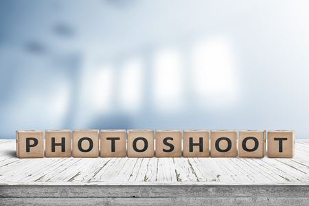 Photoshoot word sign on a wooden desk with a blurry background of a photo studio