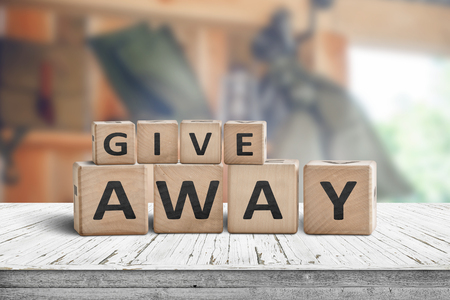 Give away contest sign on a wooden desk with stuff on a blurry background