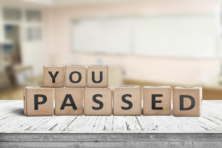 You passed sign for quiz and education purposes on a wooden desk in a bright class room