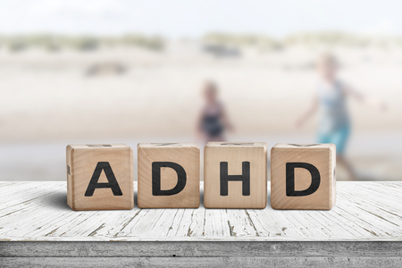 ADHD sign on a wooden table with kids acting wild in the background Stock Photo