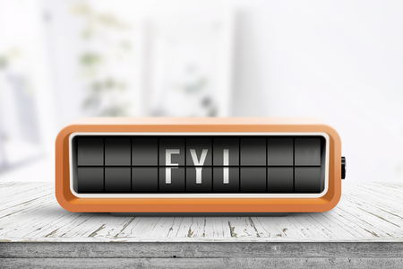 FYI message on an orange alarm clock with analog flip system on a wooden table in a bright room