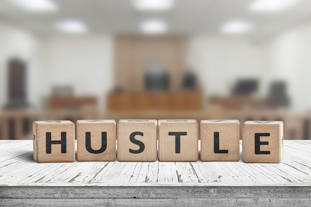 Hustle sign with text on a worn desk in a courtroom with bright lights