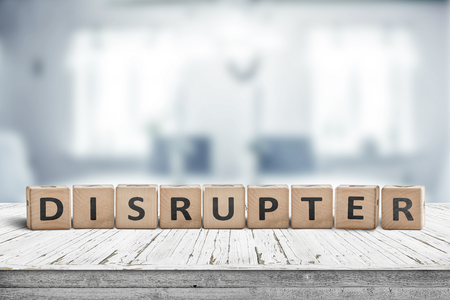 Disrupter sign on an office desk on a bright blue room in daylight Imagens