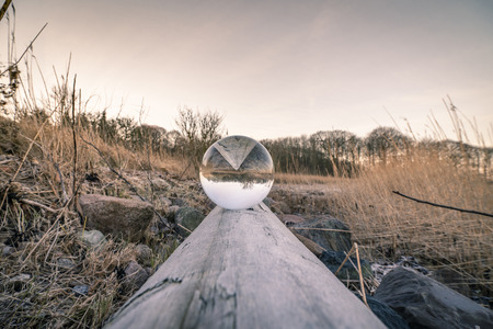 Crystal ball in balance on a wooden log in the nature by a lake Foto de archivo