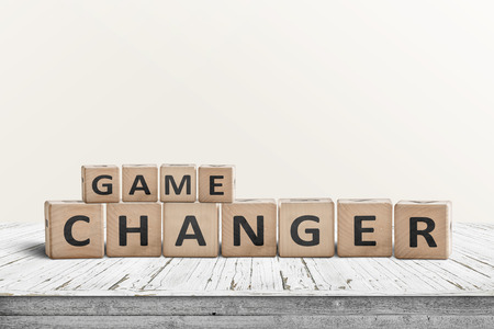 Game changer sign made of wooden blocks on a desk in a bright room Banque d'images