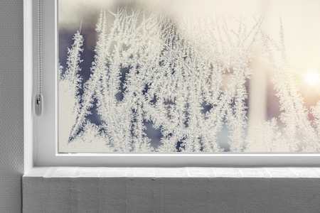 Frosty window seen from the inside with a white windowsill in the winter Imagens