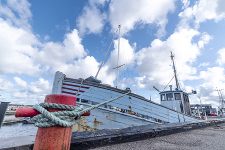 Fishing boat in a Scandinavian harbor in retro blue colors under a blue sky Stock Photo