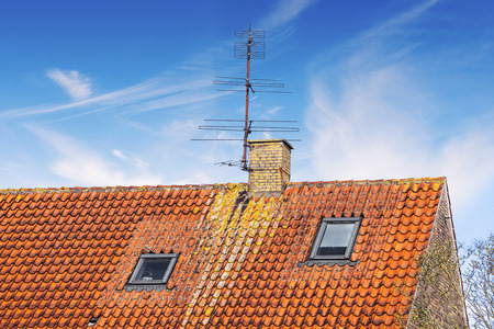 Rooftop with an antenna and a chimney under a blue sky in the summer with two small windows beneath Stok Fotoğraf