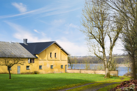 Yellow farm house by a lake in the spring with a green lawn in the yard